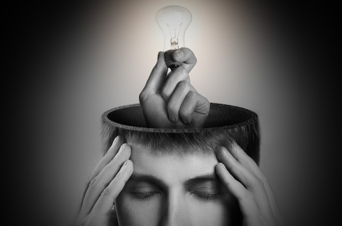 Hand with lit bulb reaching out of a head in black & white